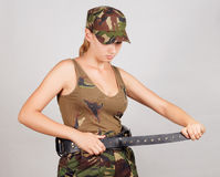 The girl in the military, buttons bandolier. Gray background. Royalty Free Stock Photos
