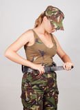 The girl in the military, buttons bandolier. Gray background. Stock Photography