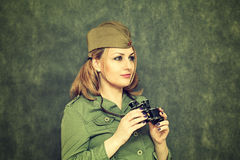 The girl in military clothes, in his cap, with binoculars. Victory Day on May 9 Royalty Free Stock Image
