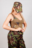 The girl in military clothes unbuttoned pants. Gray background. stock images