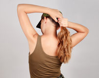 Girl in military dress corrects hair in a ponytail. Gray background. Royalty Free Stock Photos