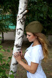 Girl in a military garrison cap about a birch Royalty Free Stock Photography