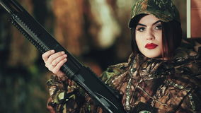 Girl in a military uniform and with a pump-action shotgun. posing on camera. stock footage
