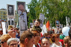 A girl in military uniform sits on shoulders of her father in the action `Immortal regiment` on Victory day in Volgograd. Volgograd, Russia - May 09, 2016: A royalty free stock image