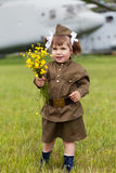Girl in a military uniform with wild flowers in a Stock Photos