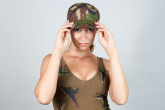 The girl in the military vest and a cap. Gray background. Stock Photo