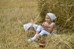 Girl with milk and fritter in field Royalty Free Stock Image