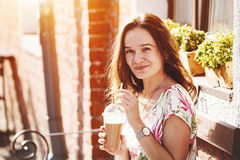 Girl with milk shake sitting at street Stock Photography