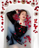 Girl milk water bath red roses candles Stock Image