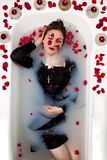 Girl milk water bath red roses candles Stock Photos