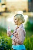Girl with milkshake in park Stock Image