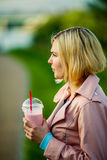 Girl with milkshake on street Stock Images