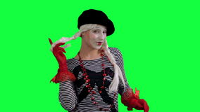 The girl mime flirting funny. The girl mime against a green background stock footage