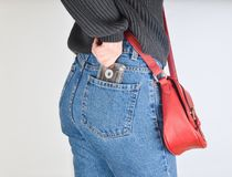 A girl in a mimes fit jeans, a sweater and with a red bag on the edge pulls out a retro audio cassette from her pocket stock images