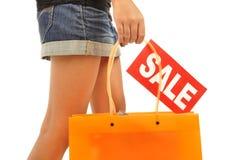 Young woman, mini skirt, orange bag Stock Image