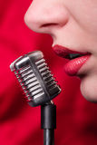 Girl and miniature microphone Stock Images