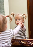 Girl and mirror. Little girl touch her reflection in front of the mirror Royalty Free Stock Image