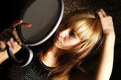 Girl at the mirror. The girl is looking herself at the mirror to apply her make-up Royalty Free Stock Images