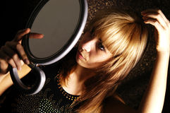 Girl at the mirror. The girl is looking herself at the mirror to apply her make-up Royalty Free Stock Photo