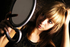 Girl at the mirror. The girl is looking herself at the mirror to apply her make-up Royalty Free Stock Image