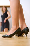Girl in the mirror. A girl fitting dress and shoes in front of a mirror. Focus on the foreground stock photo