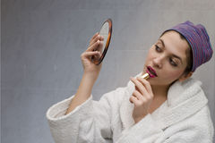 Girl-at-the-mirror. The girl is in the bathroom looking herself at the mirror to apply her make-up stock photos