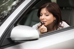 Girl in a mirror of car of a painting lip Royalty Free Stock Photo