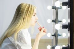 The girl at the mirror does makeup. Blonde with long hair in profile. Cosmetic pencil in the hands royalty free stock image