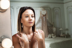 Girl before the mirror. Half-naked girl in front of a mirror in the bedroom. hanging over the bed of her dress Royalty Free Stock Photo