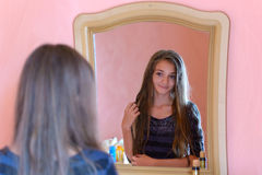 Girl and mirror. The girl looks in the mirror Royalty Free Stock Photography