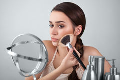 Girl in the mirror puts makeup brush. Girl, woman in the mirror puts makeup brush Stock Image