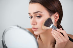 Girl, in the mirror puts makeup brush. Girl, woman in the mirror puts makeup brush Royalty Free Stock Image