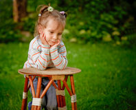 Girl misses on mum. Little girl on a green lawn leans against chair and thinks of mother Stock Photography