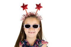 Girl missing front teeth with patriotic red star headband. Young girl missing front teeth with red star headband and dark glasses Royalty Free Stock Images