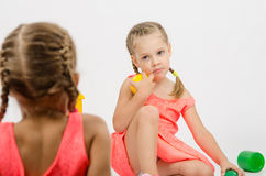Girl misunderstanding looks at her sister while playing with toys Stock Image