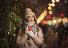 A girl in mittens and a hat holds a red coffee mug next to a Christmas tree