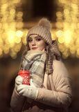 A girl in mittens and a hat holds a red coffee mug