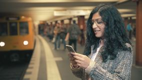 The girl of the mixed race awaits the train on the platform of the subway and touches the screen of the smartphone. Beautiful brunette mixed race girl in the stock footage