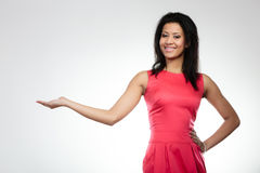 Girl mixed race holding open palm. Beauty, fashion, advertisement concept - young woman girl mixed race african caucasian in red dress holding open palm, empty Royalty Free Stock Photos