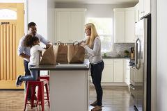 Girl and mixed race parents unpack shopping bags in kitchen royalty free stock images