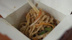 The girl mixes udon with chicken with wooden chopsticks in a takeaway box. stock video