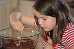 Girl mixing cake. Little girl mixing the ingredients of a chocolate cake royalty free stock images