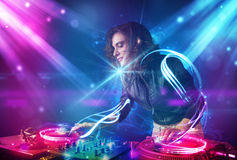 Girl mixing music with powerful light effects. Energetic  girl mixing music with powerful light effects Royalty Free Stock Photos