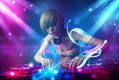 Girl mixing music with powerful light effects. Energetic Dj girl mixing music with powerful light effects Royalty Free Stock Images