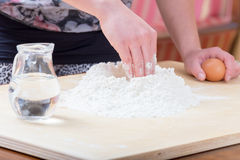 Girl is mixing the water and flour. The girl is mixing by hand the water and flour to make the dough for preparing handmade fresh pasta stock photos