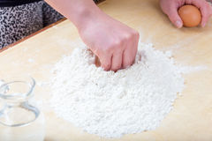 Girl is mixing the water and flour. The girl is mixing by hand the water and flour to make the dough for preparing handmade fresh pasta royalty free stock photo