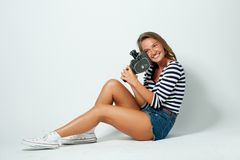 Girl with an 8mm retro movie camera Royalty Free Stock Image