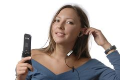 A girl with mobile phone. Is listening to the music through the headphones Stock Image