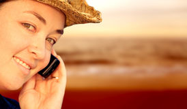 Girl on mobile phone by the beach Stock Image