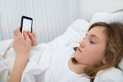 Girl With Mobile Phone In Bedroom Stock Images
